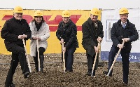 DHL managers and local officials <p>dig in for the new Linz facility